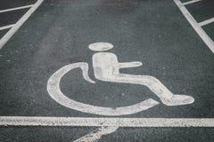 Det handikappade/rörelsehindrade parkeringstecknet målade på vägasfalten Royaltyfri Bild