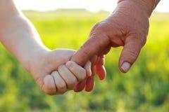 Det Hans barnet och pensionären över vetesommar field Arkivfoton