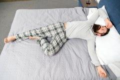 Det har varit en l?ng natt mogen man med sk?gget i pajama p? s?ng sovande och vaket energi och tr?tthet sk?ggig man royaltyfri foto