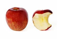 Det hela röda äpplet och biten äpplet arkivfoton