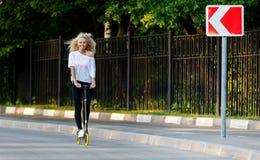Det hellånga fotoet av denhaired idrotts- kvinnan som sparkar på sparkcykeln parkerar in arkivbilder