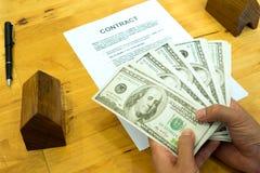 Det hem- köpandebegreppet, dollar och modellhus med avtalet skyler över brister Royaltyfri Foto