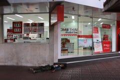 Det hemlösa folket sover i framdel av den THAILÄNDSKA banken för CIMB på Yaowarat Arkivbild