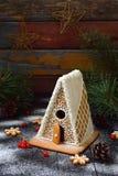 Det hemlagade pepparkakahuset med sörjer filialer, kottar och kex på mörk bakgrund Europeiska jultraditioner Xmas-ferie arkivbild