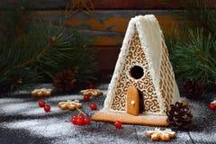 Det hemlagade pepparkakahuset med sörjer filialer, kottar och kex på mörk bakgrund Europeiska jultraditioner Xmas-ferie royaltyfri bild