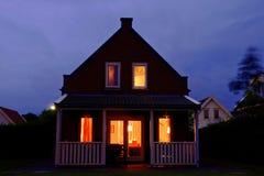Det hemtrevliga feriehemmet med verandan tände vid natt royaltyfri fotografi