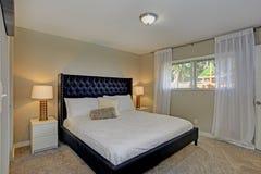 Det hemtrevliga sovrummet presenterar en svart säng och beigea väggar arkivbilder