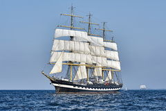 Det högväxta skeppet seglar under med kusten Arkivfoto