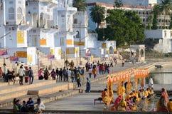 Det hinduiska folket utför pujaen (rituell ceremoni) i aftonen, på den heliga Pushkar Sarovar sjön, Indien Arkivfoton