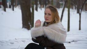 Det härliga barnet modellerar på en fotofors i vintern i en snöhäftig snöstorm cold mycket arkivfilmer