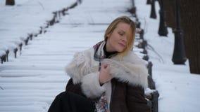 Det härliga barnet modellerar på en fotofors i vintern i en snöhäftig snöstorm cold mycket stock video