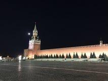 Det huvudsakliga tornet av MoskvaKreml, Ryssland med enorma klocka-chimes och en vägg av röd tegelsten mot svart den natthimmel o arkivfoton