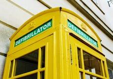 Det Iconic brittiska röda telefonbåset repurposed som en defibrillatorstation och en målad guling arkivfoto