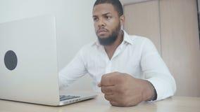 Det ilskna afrikansk amerikanframstickandet slår hans näve på tabellen Hot av våld Framstickandet visar agression lager videofilmer
