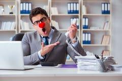 Det ilskna frustrerade arbetet för clownaffärsman i kontoret royaltyfri foto