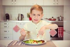 Det ilskna hungriga pojkebarnet klagar om maten royaltyfri bild