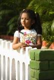 Det indiska flickaanseendet i parkerar att vila hennes händer på trädgårdstaketet, Pune royaltyfri fotografi