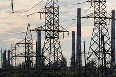 Det industriella landskapet med kraftledningar i bakgrunden leda i rör raffinaderiet arkivfoton