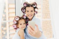 Det inomhus skottet av den angenäma seende mumen med positivt uttryck och hennes dotter gör lockiga frisyrer, poserar för selfie  royaltyfri bild