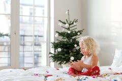Det inomhus skottet av den blonda lockiga lilla ungen sitter korsade ben på bekväm säng, spelar med färgglad legitimationshandlin fotografering för bildbyråer