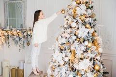 Det inomhus skottet av den lilla ungen i vitkläder, dekorerar det nya året tr arkivbild