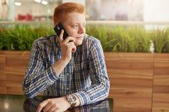 Det inomhus skottet av den stiliga unga affärsmannen med rött hår borstade tillbaka i en iklädd stilfull kontrollerad skjorta för Fotografering för Bildbyråer