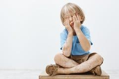 Det inomhus skottet av det gulliga europeiska barnet med älskvärd frisyr och vitiligo som täcker framsidan med, gömma i handflata royaltyfria foton