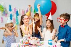 Det inomhus skottet av lyckliga glade barn ser den stora gnistrandet på kakan, firar födelsedag, bär konstiga stora anblickar, pa royaltyfria foton