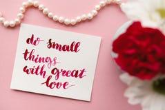 Det inspirerande citationstecknet gör liten saker med stor förälskelse som är handskriven i kalligrafistil med vattenfärgen Blom- fotografering för bildbyråer