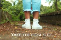 Det inspirerande motivational citationstecknet tar första steg Med fot av den unga kvinnan i vita gymnastikskor som står från til royaltyfri fotografi