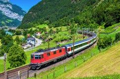 Det Intercity drevet klättrar upp den Gotthard järnvägen - Schweiz royaltyfri foto