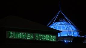 Det irländska för Dunnes för den återförsäljnings- jätten märket diversehandel tänder upp signagen Arkivfoton