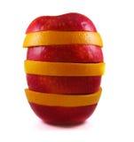 Det isolerade äpplet och grapefrukten skivar ställningar på tabellen på en vit bakgrund Royaltyfri Foto