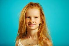 Det isolerade skottet av den gulliga röda haired flickan med roliga fräknar, trevligt uttryck, ser av in i avståndet Royaltyfria Foton