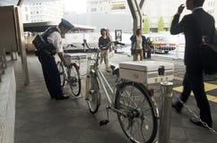 Det japanska polisfolket som stoppar cykeln efter cykel, cyklar c Arkivbilder