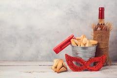 Det judiska feriePurim begreppet med hamantaschen kakor eller hamansöron, karnevalmaskeringen och vinflaskan arkivbilder