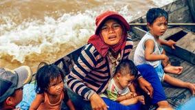 Det kambodjanska folket bor på Tonle underminerar sjön i Siem Reap, Cambodja Den kambodjanska familjen på ett fartyg nära fiskelä Arkivfoto
