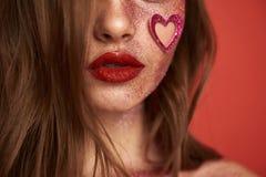 Det kantjusterade fotoet av den glamor?sa modellen med glansigt bl?nker makeup inomhus arkivbild