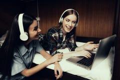 Det kantjusterade fotoet av flickor lyssnar till musik på säng arkivbild