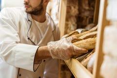 det kantjusterade skottet av att sätta för bagare släntrar av bröd på hylla royaltyfria bilder
