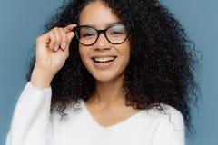 Det kantjusterade skottet av bra se kvinnan bär optiska exponeringsglas, leenden i huvudsak, visar vita perfekta tänder, sund mör royaltyfri fotografi