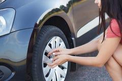 Det kantjusterade skottet av den kvinnliga chauffören för brunetten som går att ändra gummihjulet för den plana bilen, har proble Arkivfoton