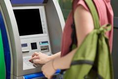Det kantjusterade skottet av den kvinnliga tonåringen bär den gröna påsen, önskar att återta kassa, står den near ATM-maskinen, s arkivfoto