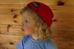 Det kantjusterade skottet av ett gulligt litet behandla som ett barn pojken med lockigt hår som bär Red Hat royaltyfria bilder