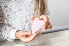 det kantjusterade skottet av hållande hjärta för flickan formade kakan fotografering för bildbyråer