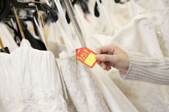Det kantjusterade skottet av kvinnlign räcker den hållande prislappen som fästas till bröllopkappan i brud- boutique Royaltyfri Bild