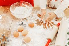 Det kantjusterade skottet av det lilla barnet i förkläde bakar något som är läcker på kök, gör kakor med händer som omges med arkivbild