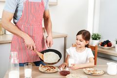 Det kantjusterade skottet av mannen i förklädet som är involverat i matlagning, läckra pannkakor för småfiskar för hans dotter, p royaltyfri bild