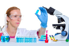 Det kemiska arbetet för laboratoriumforskarekvinnan med buteljerar Arkivbild