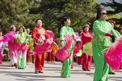 Det kinesiska folket i färgrikt traditionellt silke beklär dans Arkivfoton